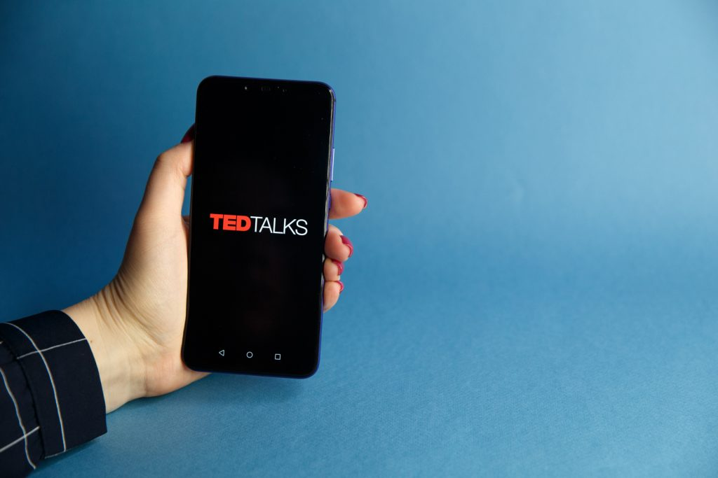 woman holding smartphone with ted talks on screen