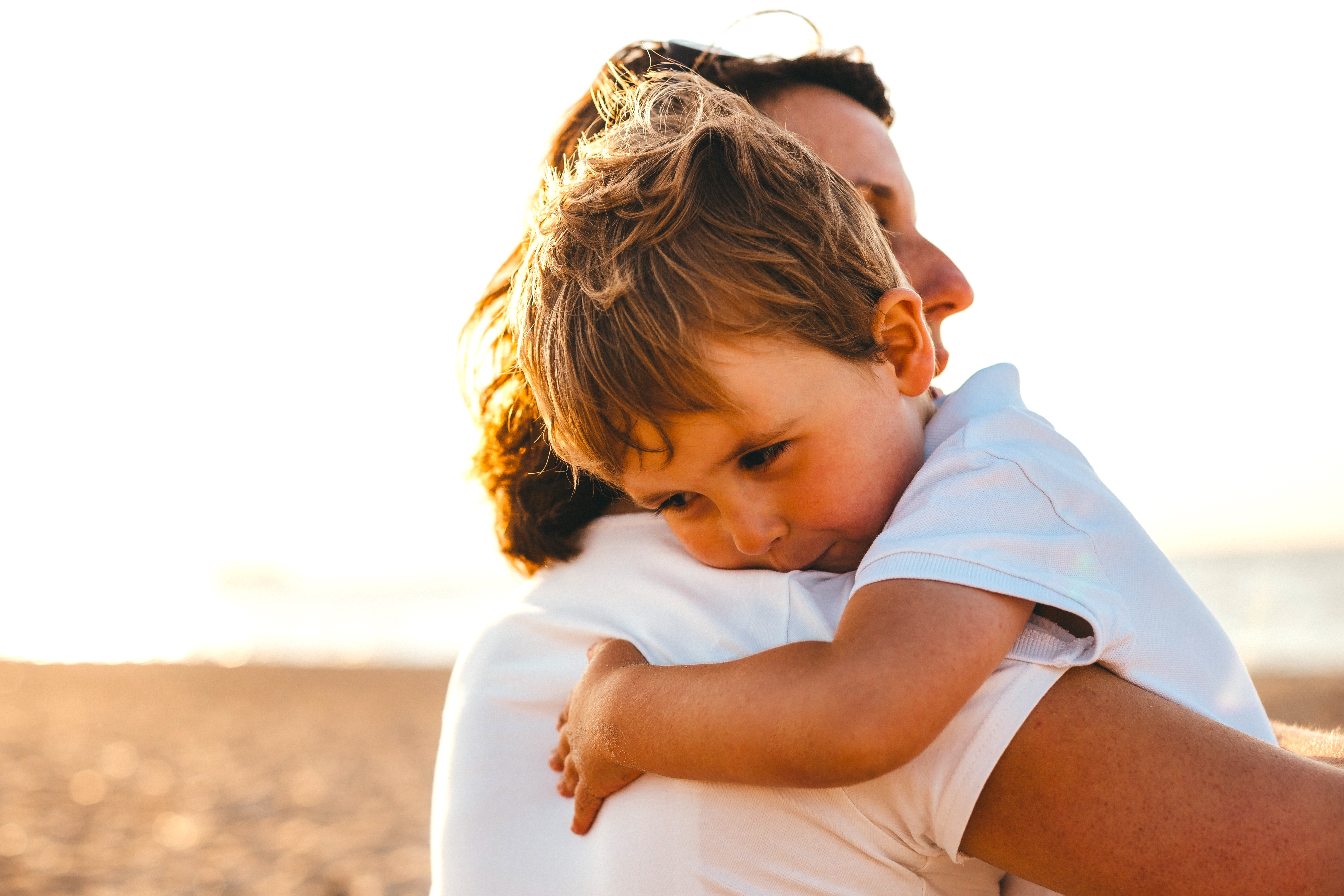 Mom hugging her son on the beach